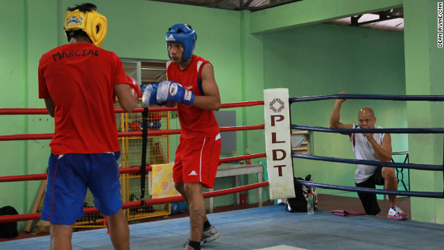 Coach Ronald Chavez watches as Filipino World Junior Champion Eumir Marcial (left) is put through his paces in the ring.