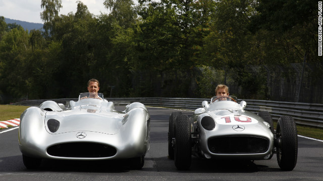 Michael Schumacher in the modern Silver Arrow while Mercedes teammate Nico Rosberg takes the wheel of the 1955 model.