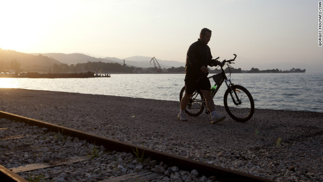 A man walks along the waterfront in Aigio, Greece, on March 31, 2010