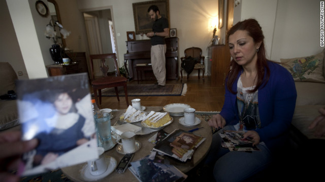 "Sissy Papathanasopoulou with photographs of Angeliki. Her younger sister, four months pregnant when she died, was ""very happy,"" Sissy says."