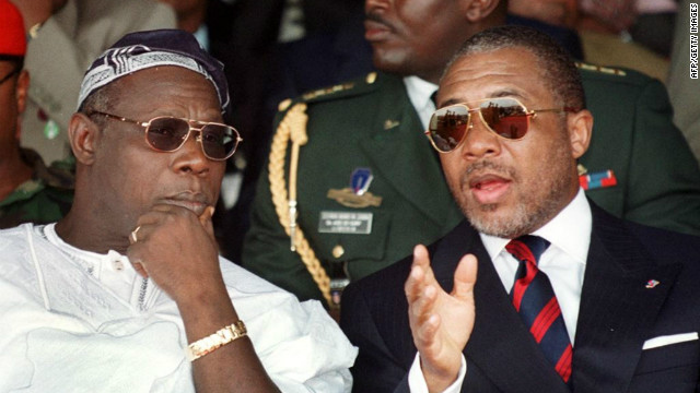 Liberian President Charles Taylor, right, chats to Nigerian counterpart Olusegun Obasanjo during a symbolic bonfire to destroy weapons in Monrovia in July 1999.