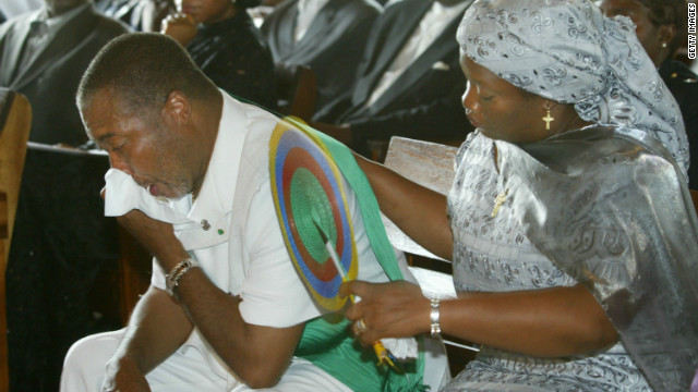 Charles Taylor is comforted by his wife, Jewel Howard-Taylor, at the funeral of his mother in July 2003 in Monrovia.