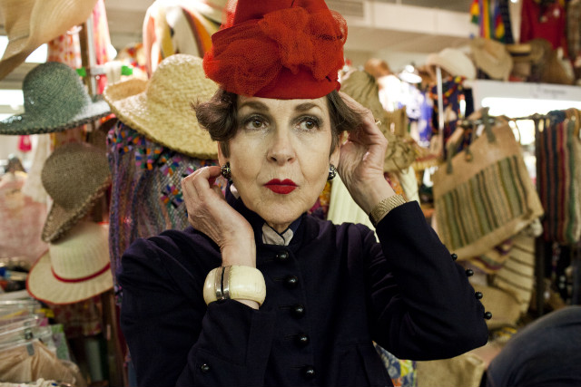 Tziporah Salamon, 62, looks at herself in a mirror as she tries on a new hat at the Manhattan Vintage Clothing Show.