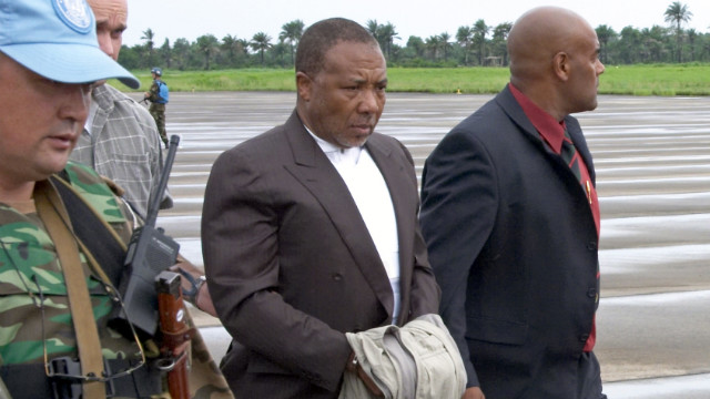 Liberian ex-President Charles Taylor is escorted at the Freetown, Sierra Leone, airport on his way to the Netherlands in 2006.