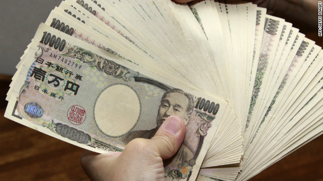 A bank teller counts 10,000 yen bank notes in Tokyo.