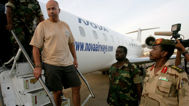 One of the four foreigners captured whilst investigating debris from recent fighting between Sudan and South Sudan in the Heglig oilfield area on April 28, 2012, is escorted off an airplane by Sudanese soldiers in Khartoum.