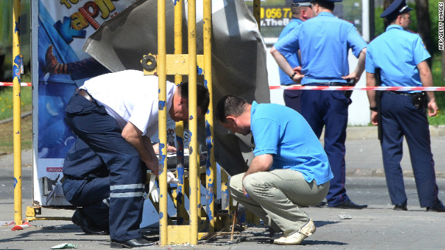 Police experts examine one of the explosion sites in Dnipropetrovsk, where four bombs were let off in rubbish bins on Friday. At least 30 people were injured, raising serious concerns over safety at next month's European Championships.
