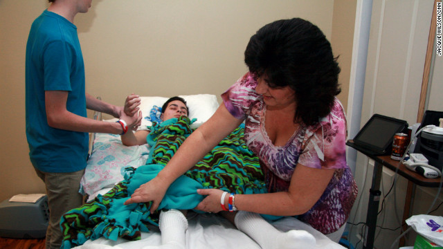 Janine Buchanan adjusts the blanket on her son's bed as Curtis helps Ryan with physical therapy. 