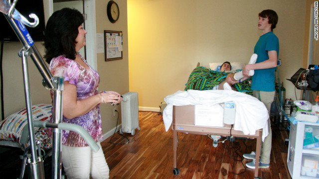 Curtis Hunter, a church friend who was with Ryan on the day of the accident, helps keep the teen's limbs from atrophying through physical therapy, while mom Janine Buchanan watches.