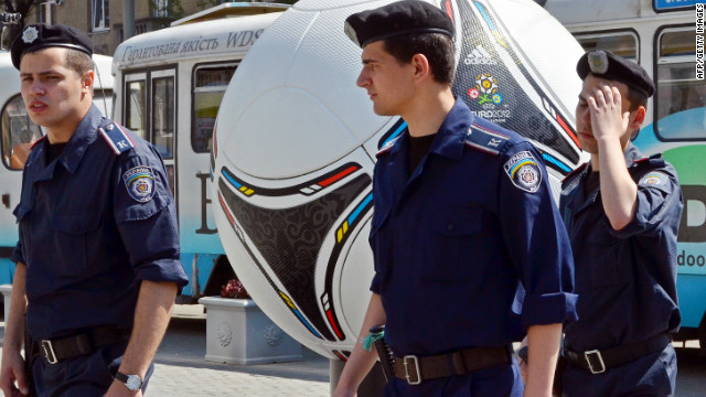 "Police officers walk past a giant model of ""Tango 12,"" the official match ball of the Euro 2012 football tournament, during a patrol in Dnipropetrovsk on April 29. No group has yet claimed responsibility for the bomb attacks."
