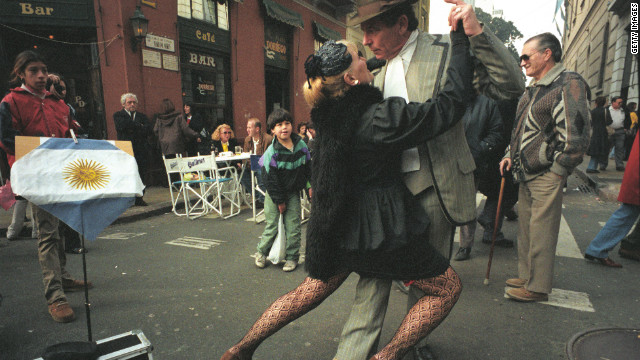 "An old couple dressed in immaculate 1920s garments do the tango in the middle of San Telmo street while a young boy looks on. Migdalia Romero, author of the ""Tango Lover's Guide to Buenos Aires"" says that, to this day, tango is loved by all generations across the city."