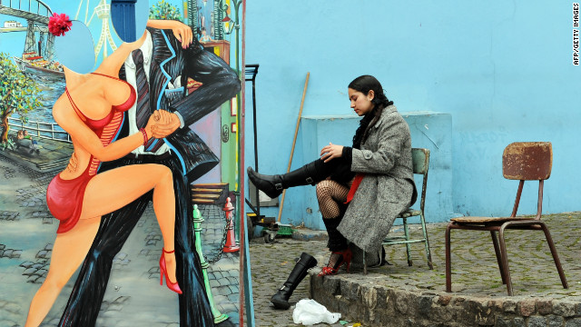 A tango dancer changes her boots for high-heeled shoes before a performance at Caminito Street in the La Boca neighborhood -- widely known for the football club Boca Juniors -- and for its vivid tango-themed murals.