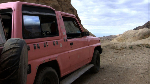 Al-Bedoul's bright pink jeep, &quot;the couch surfing flag,&quot; is parked outside.