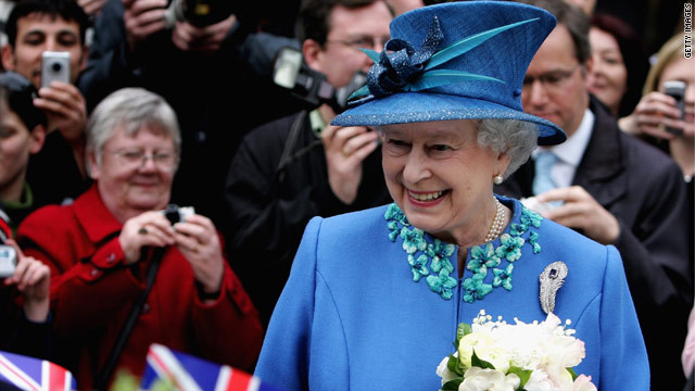 Queen Elizabeth II leaves the BBC Broadcasting House, London in 2006 wearing her trademark ensemble of monochromatic color and matching coat and hat.