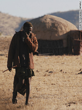 Himba homes are round structures constructed of sapling posts, which bound together to form a conical roof plastered in mud and dung.