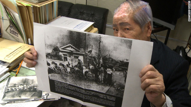 Sunao Tsuboi, who suffered horrific burns in Hiroshima, holds a photo of himself and friends taken hours after the explosion.