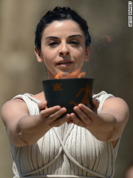 The priestess, played by Greek actress Ino Menegaki, lifts the &quot;Archaic Pot&quot; from which the flame is lit. 