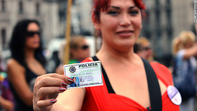 Walter Daniel Alvarez shows his police credential whilst waiting outside Congress in Buenos Aires, on May 9, 2012.