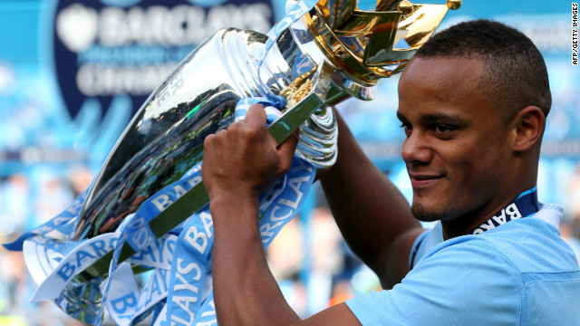 Victorious captain Vincent Kompany holds aloft the Premiership trophy ...