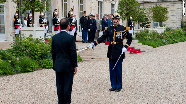 Hollande reviews the troops after officially becoming France's new president at the lyse Palace.