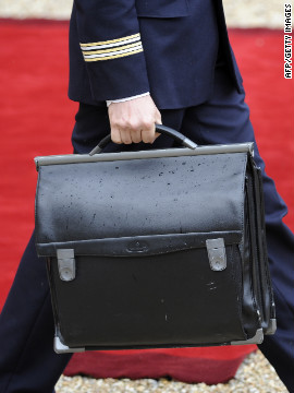 The French president's nuclear satchel is carried through the lyse Palace.