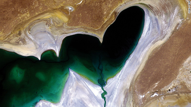 A satellite image features the heart-shaped northern tip of the western half of the Large Aral Sea (or South Aral Sea) in Central Asia. Once the world's fourth-largest inland body of water, the Aral Sea has been steadily shrinking over the past 50 years since the rivers that fed it were diverted for irrigation. In 2005, a dam was built between the sea's northern and southern sections to help improve water resource management and reverse the man-made environmental disaster. The dam allowed the river to feed the northern Aral, which has begun to recover. It hasn't solved the entire problem though, as the southern section is expected to dry out completely by 2020. The whitish area surrounding the lakebed is a vast salt plain, now called the Aralkum Desert, left behind by the evaporating sea. It comprises some 40 000 sq km zone of dry, white salt and mineral terrain. Each year violent sandstorms pick up at least 150 000 tonnes of salt and sand from Aralkum and transport them across hundreds of kilometres, causing severe health problems for the local population and making regional winters colder and summers hotter.