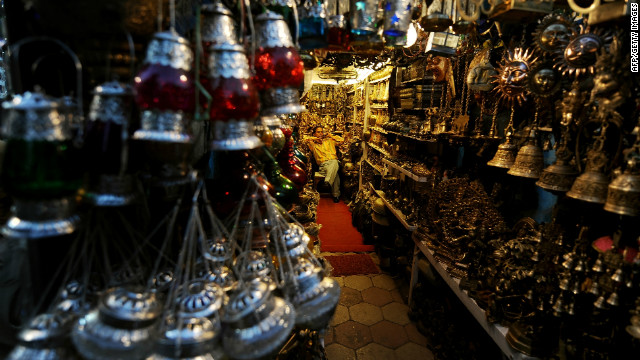 "An Indian shopkeeper waits for customers as he sells decorative goods at the popular Janpath street market. Popularly known as the ""Tibetan Market,"" it's said you'll pick up a better selection of items (from antique locks to silver jewelry) at cheaper prices here than you will anywhere in Tibet itself."
