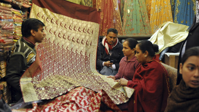 "Shoppers browse through saris for sale at a shop in Connaught Place, one of New Delhi's most prosperous centers and a consumer paradise. The ""Banarasi"" silk saris pictured here are famed for their embroidery and are still sought after by northern Indian brides for their wedding day."