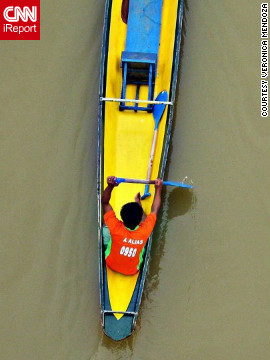 A brightly colored boat glides through Pagsanjan, Philippines, during the Bangkero Festival. The festival, a popular tourist event, celebrates Filipino boatmen and features boat parades and exhibitions.