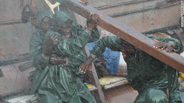 "Characters in ""La Pirogue"" weather treacherous conditions in their wooden boat."