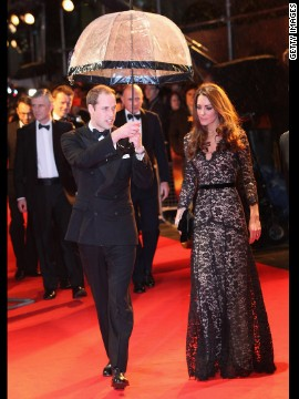"Prince William kept his wife dry at the London premiere of ""War Horse"" on January 8, 2012. She wore a black lace Alice by Temperley gown and carried a black clutch."