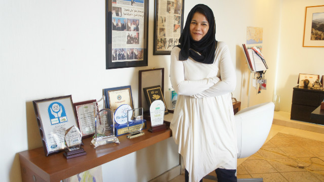 Rumman CEO Enas Hashani stands beside some of the company's awards.