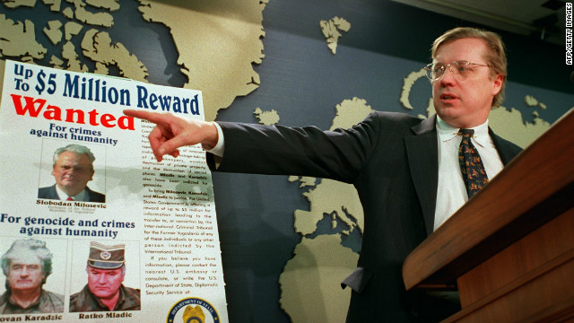David Scheffer, U.S. Ambassador at large for war crimes points to a wanted poster showing Yugoslav President Slobodan Milosevic, Karadzic and Mladic in March 2000.