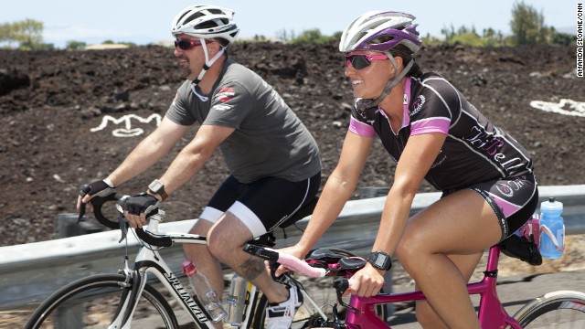 Athletic director April Burkey gives Morris some tips as they continue their bike ride.