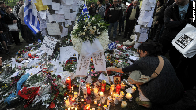People light candles and lay flowers and hand written messages on April 5, 2012 at the site where a retired pharmacist shot himself at Athens central Syntagma square on April 4, citing the austerity measures as a reason.