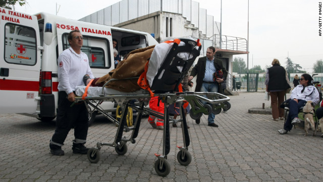 A rescuer pushes an elderly woman on a stretcher at the sports center of Finale Emilia.