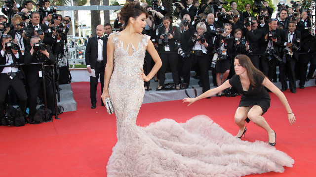 An assistant helps actress Eva Longoria with her dress on the red carpet on Wednesday.