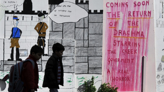Schoolchildren walk past drawings and a slogan on a wall in the center of Athens in February.