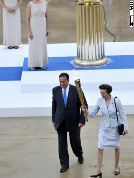 Queen Elizabeth II's daughter, Anne, the Princess Royal, receives the flame from Olympic chief Spiros Kapralos at a handover cermony in Athens on May 17.