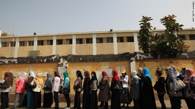Egyptian women wait outside a polling station in Cairo. Many Egyptians seem uncertain of their loyalties to any particular candidate.
