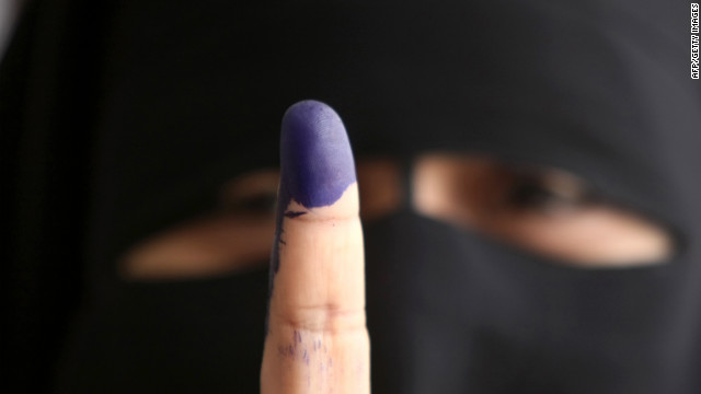 An Egyptian woman holds up an ink-stained finger after casting her ballot in Cairo on Wednesday, May 23, 2012, the first day of voting in the historic election.