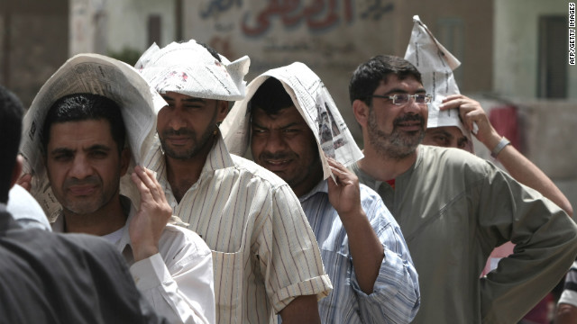 Egyptian men shield themselves from the hot sun outside a Cairo polling station Wednesday.