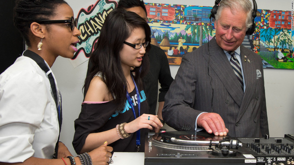 Prince Charles wears headphones as he learns how to scratch and fade with a turntable as he visits UforChange, an arts program for low-income and newcomer youth in Toronto.