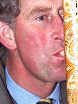 The Prince of Wales tries out a fujara, a musical instrument that he received as a gift on November 1, 2000 in Slovakia.