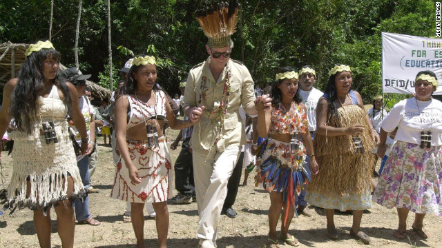 Wearing garlands and a headdress, Prince Charles dances with women of the Surama tribe on a visit to the Iwokrama rainforest in Guyana in February 2000.