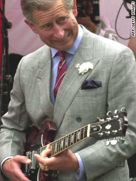 Prince Charles strums a guitar during a visit with young people and volunteers involved in projects helped by The Prince's Trust Cymru on July 19, 2002, in Cymru, Wales.