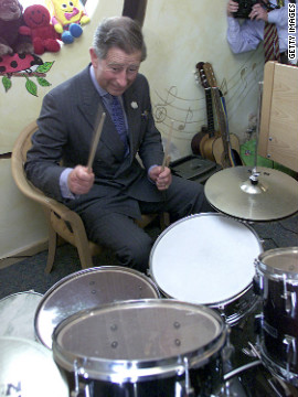 Prince Charles plays drums while visiting staff, children and their families on July 13, 2001, at Ty Hafan Children's Hospice in Sulley, Wales.