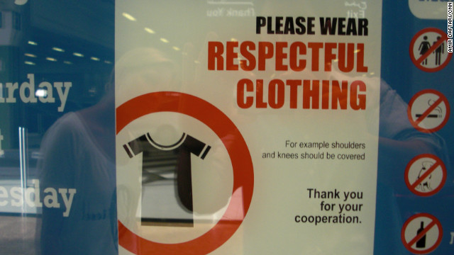 Signs in shopping malls remind visitors to cover their knees and shoulders. Some people say security guards should go further and ban or fine those who refuse to cover up.