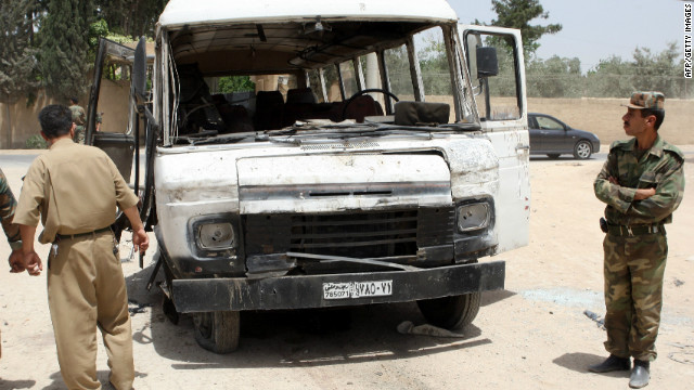 Syrian military officers inspect a damaged bus following a deadly explosion on May 23, 2012.