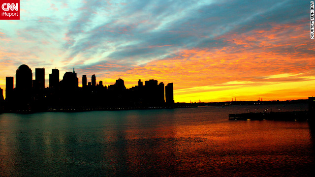 The sky over Manhattan bursts with brilliant color at dawn.